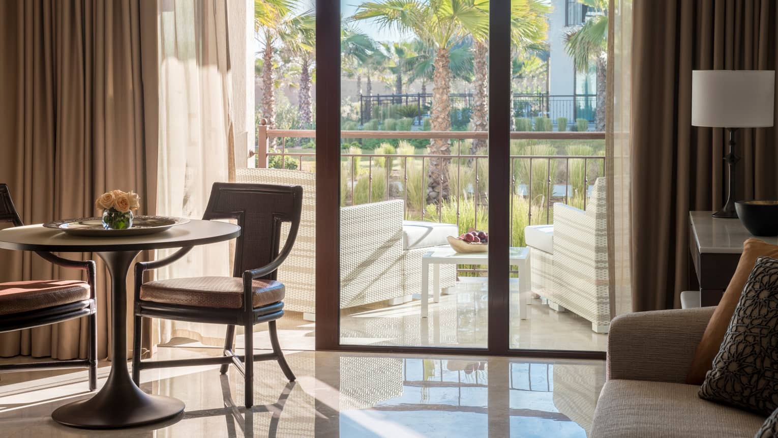 Garden-View Suite small dining table, chairs by sunny balcony doors with wicker armchairs, palm trees