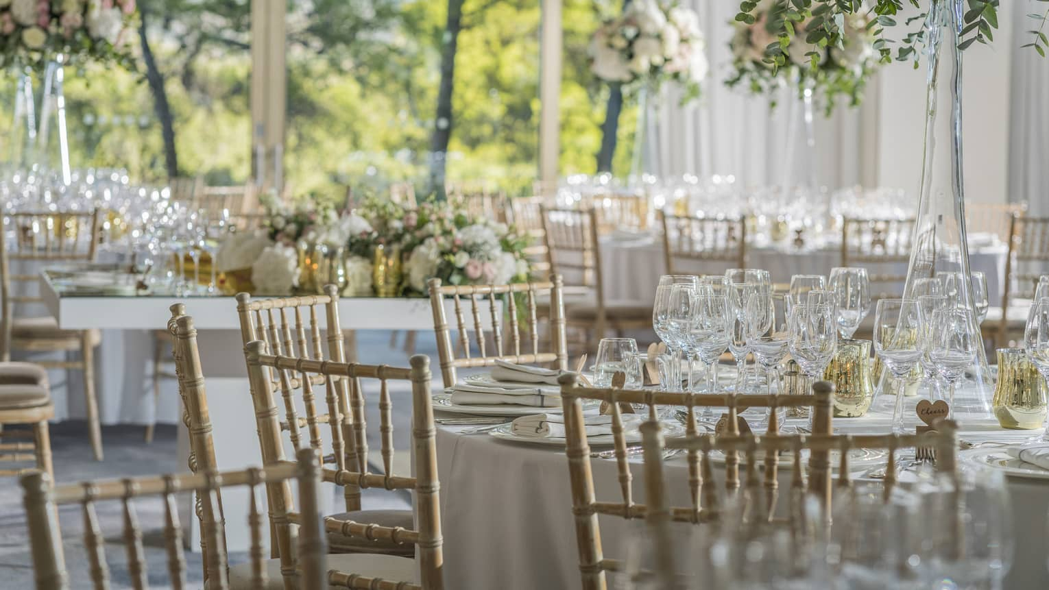 Round table with wooden chairs, place settings, glasses, floral display, in sunny room overlooking trees