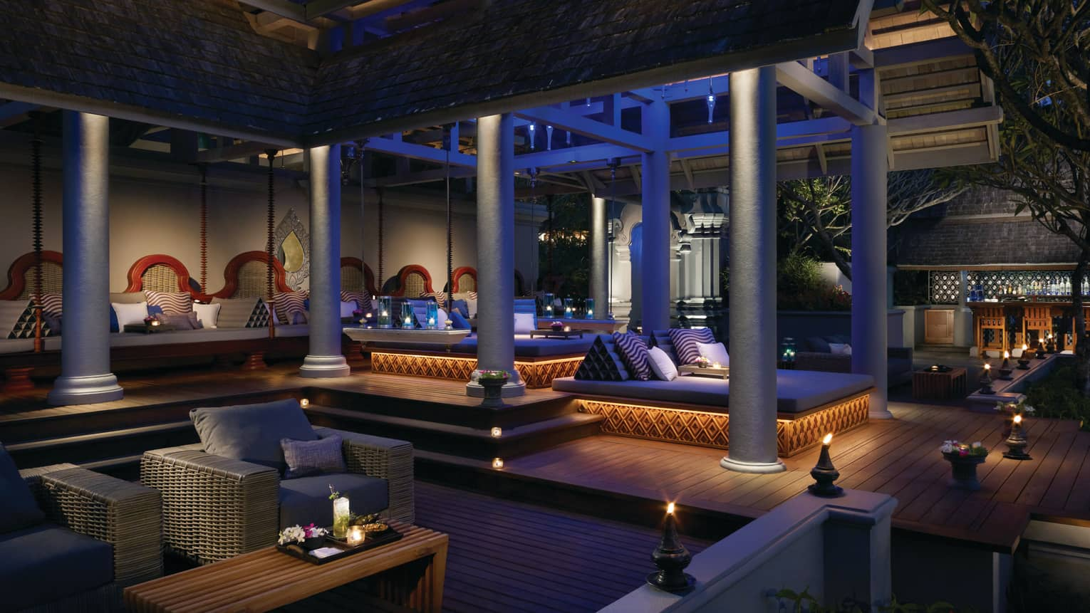 Ratree patio large wicker lounge sofas, chairs, small lanterns under white pillars at night
