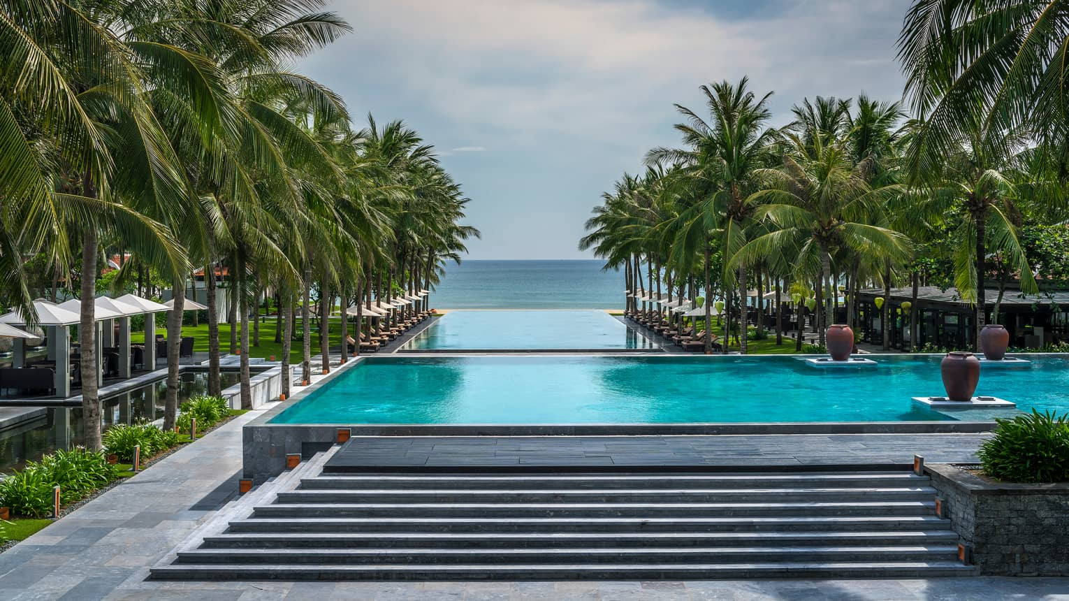 Stone stairs to outdoor infinity swimming pools, palms at Four Seasons The Nam Hai Resort
