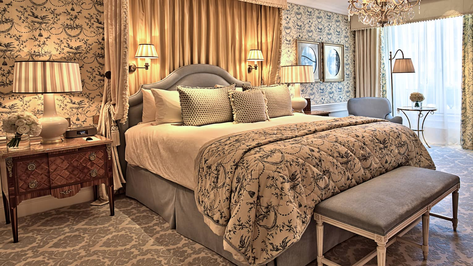 Parisian Suite bed with blue-and-white spread, headboard, draped canopy, antique-style wallpaper