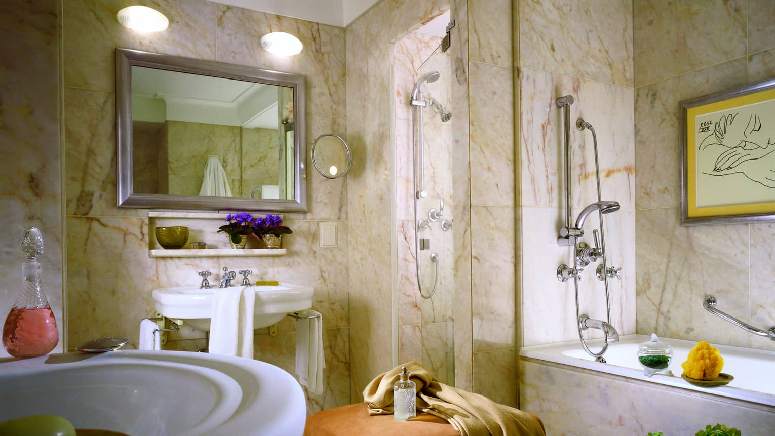 Sunny white-and-beige marble bathroom with large round sinks, bathtub and two showers