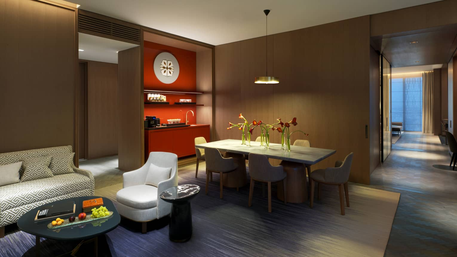 Ambassador Suite private dining table in front of wood panel bar, red wet bar, modern sofa, chair