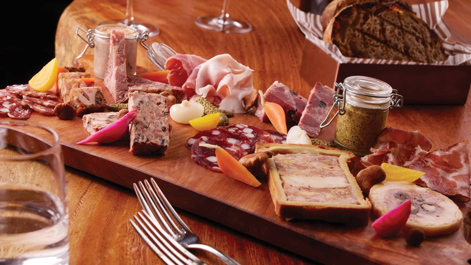 Close-up of charcuterie board with cured meats, pate, mustard