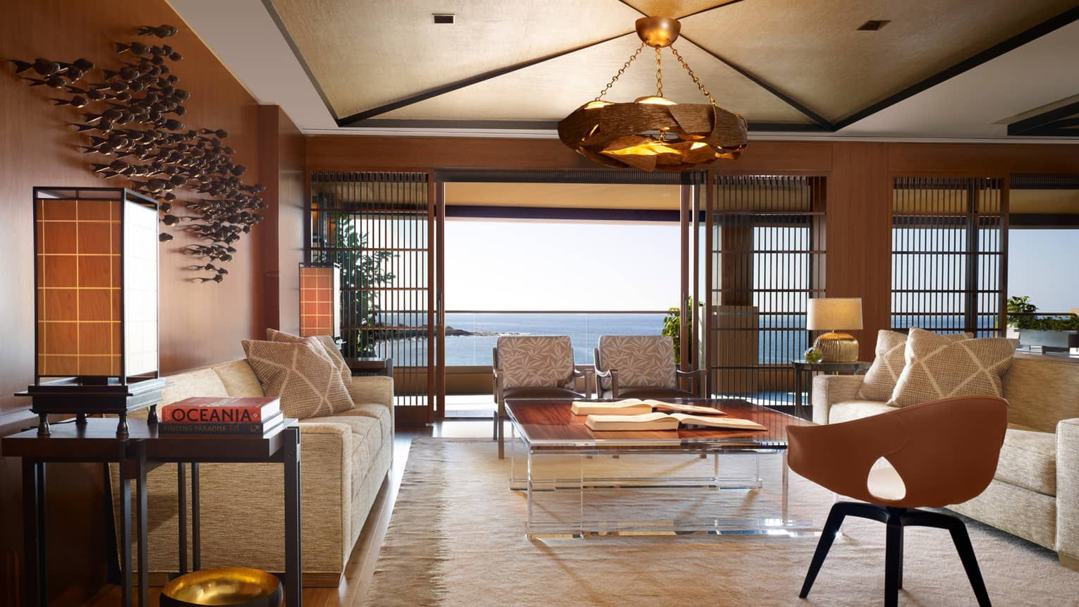 Alii Royal Suite spacious seating area with bespoke furnishings, mid-century style sofas, chairs, light