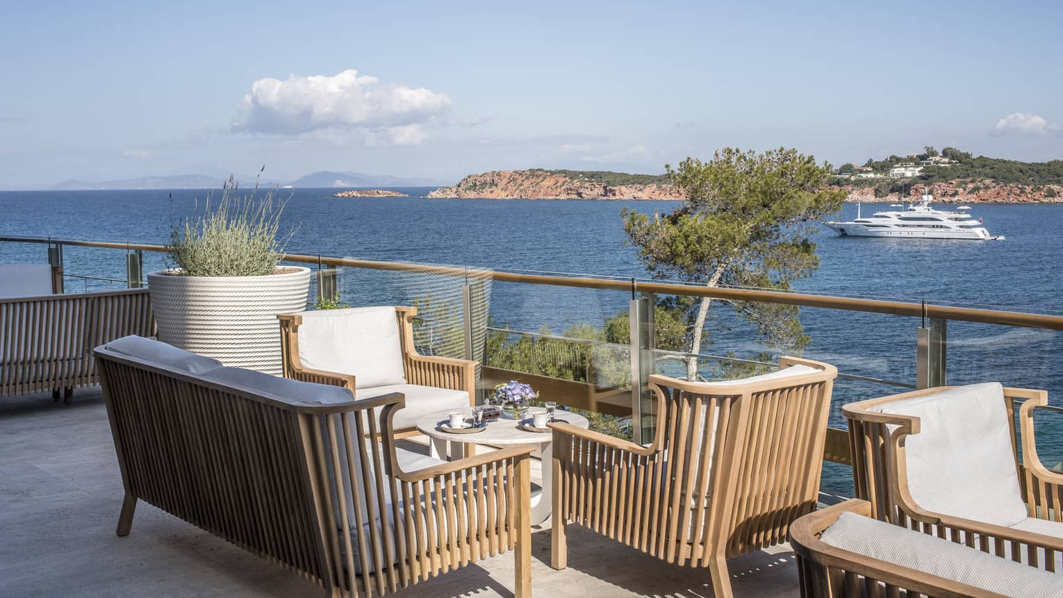 Wooden chairs with white cushions surrounding small round table by ocean with boat at Astron Terrace