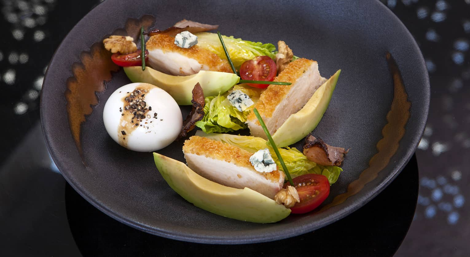 A Cobb Salad with chicken breast, a hardboiled egg, avocado, tomatoes, lettuce and blue cheese
