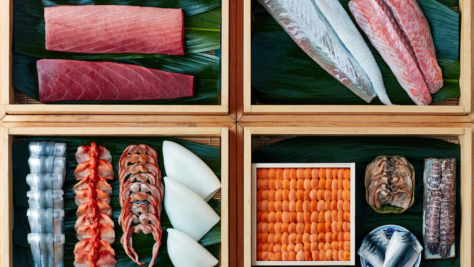 Four bamboo boxes with raw fish filets, sashimi sushi sliced fish