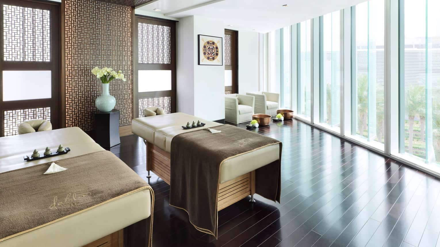 Dahlia Spa Couples Suite two massage tables with soft brown blankets in sunny room with wood floor, big windows