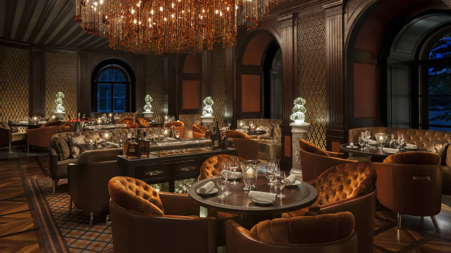 Orange velvet armchairs, brown leather sofas under elaborate chandeliers in Porcorso lounge