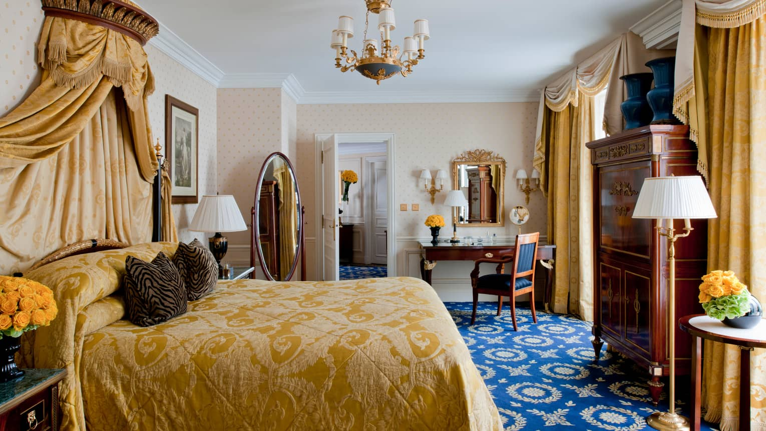 Empire Suite bed with embroidered gold bedspread, canopy across from oval floor mirror, wood dresser