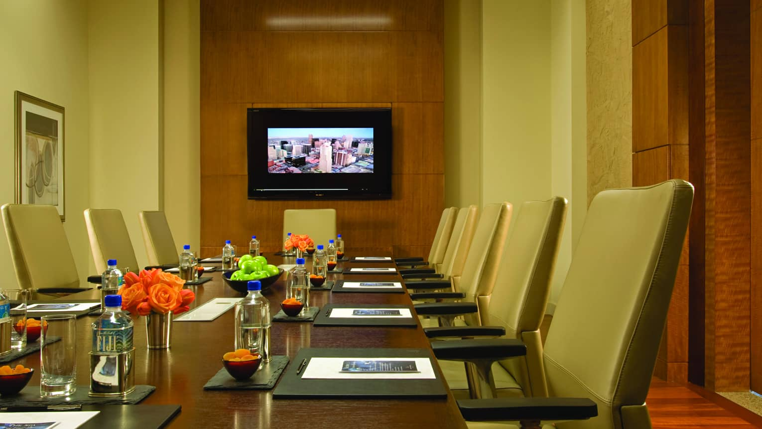 Executive boardroom table with tan leather chairs, flowers by modern wood panel wall with TV screen