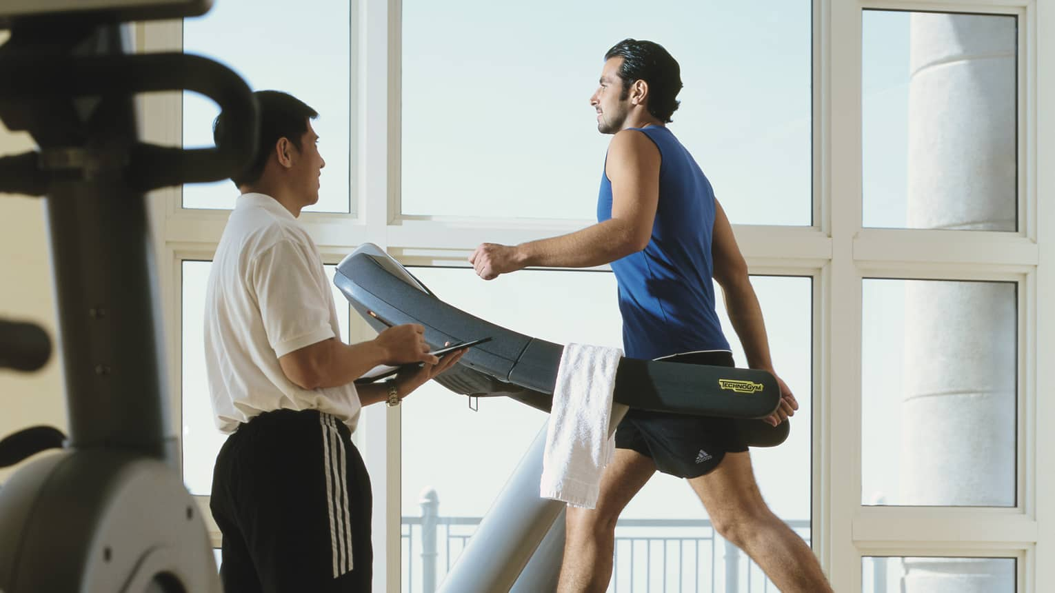 Man in workout gear on treadmill as personal trainer looks on