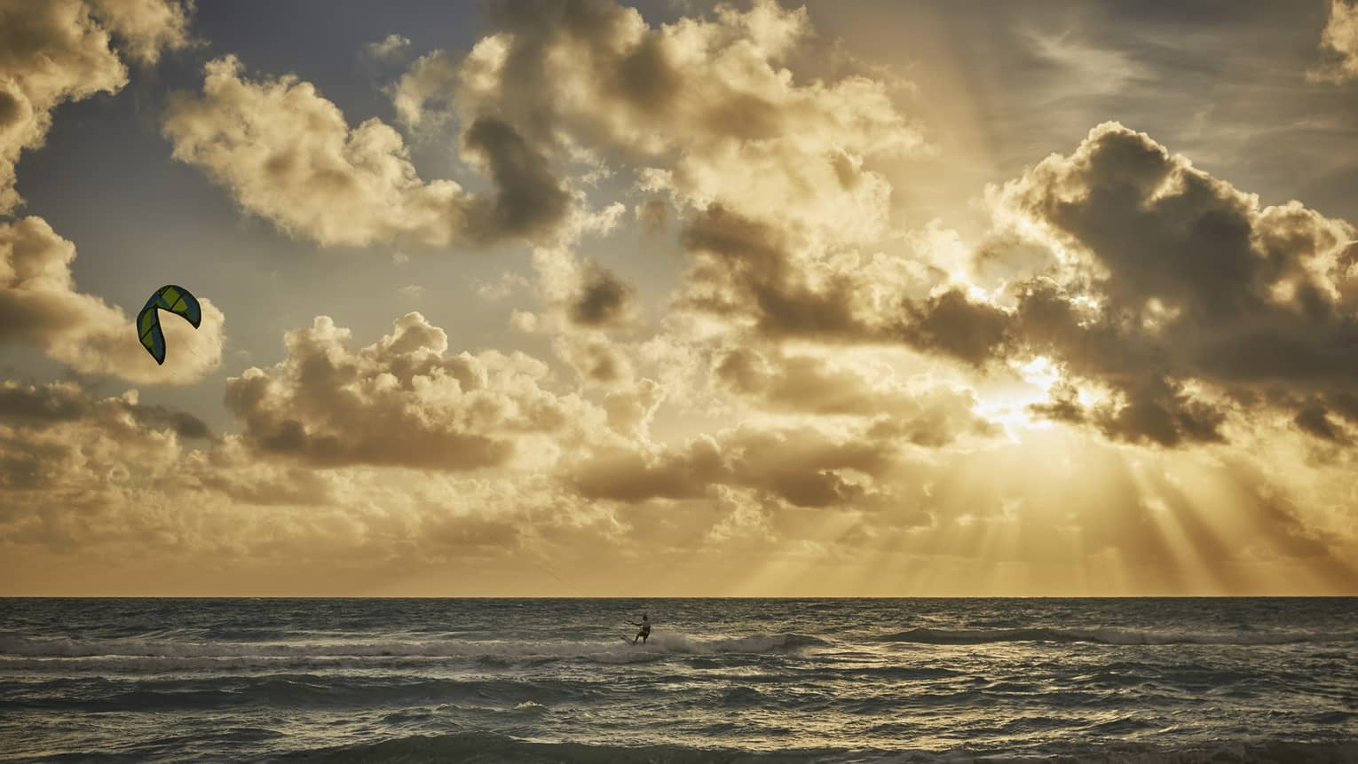 A four seasons guest windsurfs into the sunset over the ocean