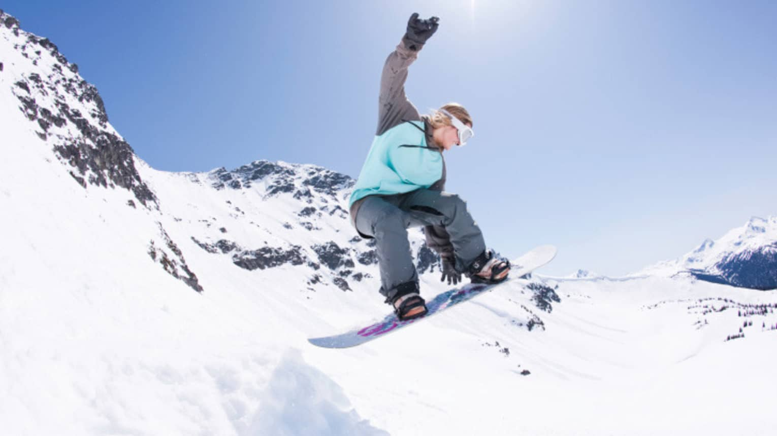Snowboarder jumps, grabs board in mid-air on sunny mountain peak