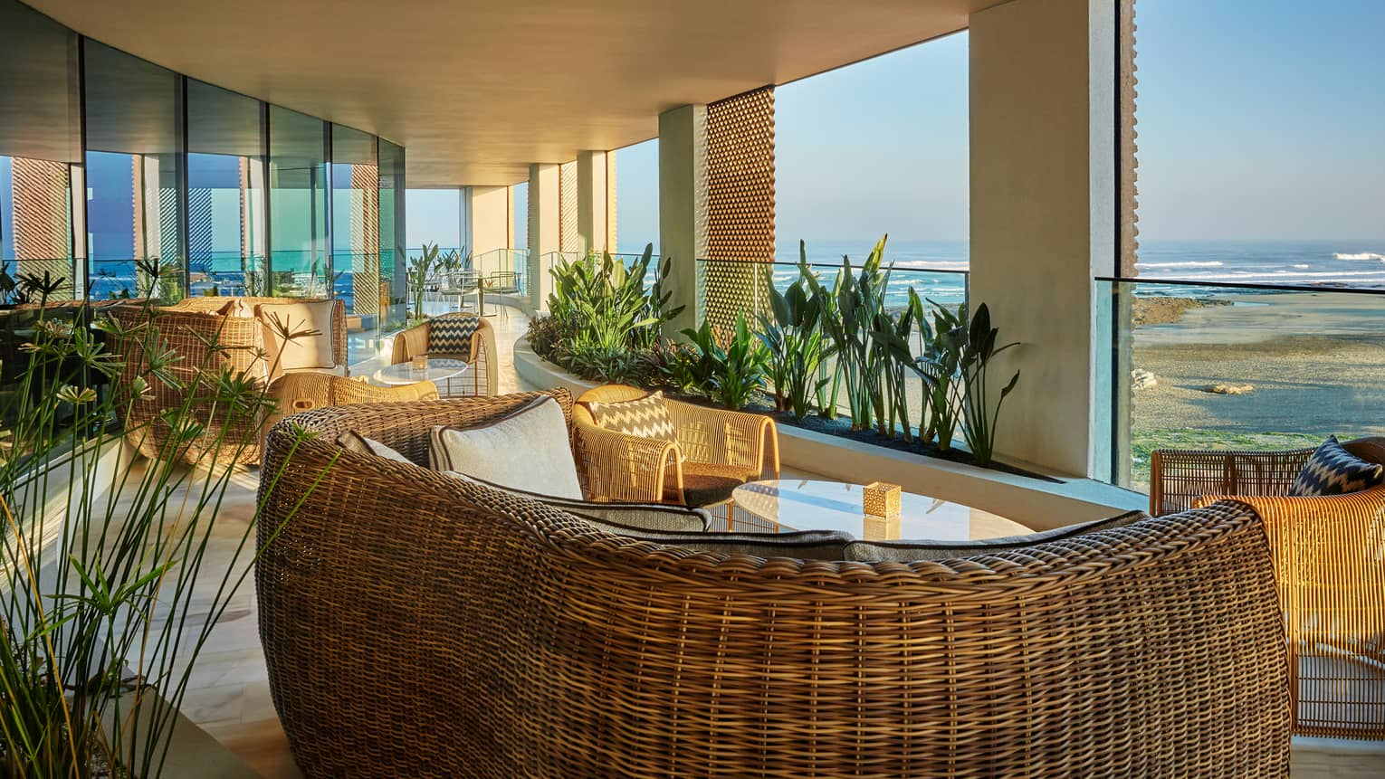 Bleu patio with large wicker sofas, chairs, tropical plants, beach views
