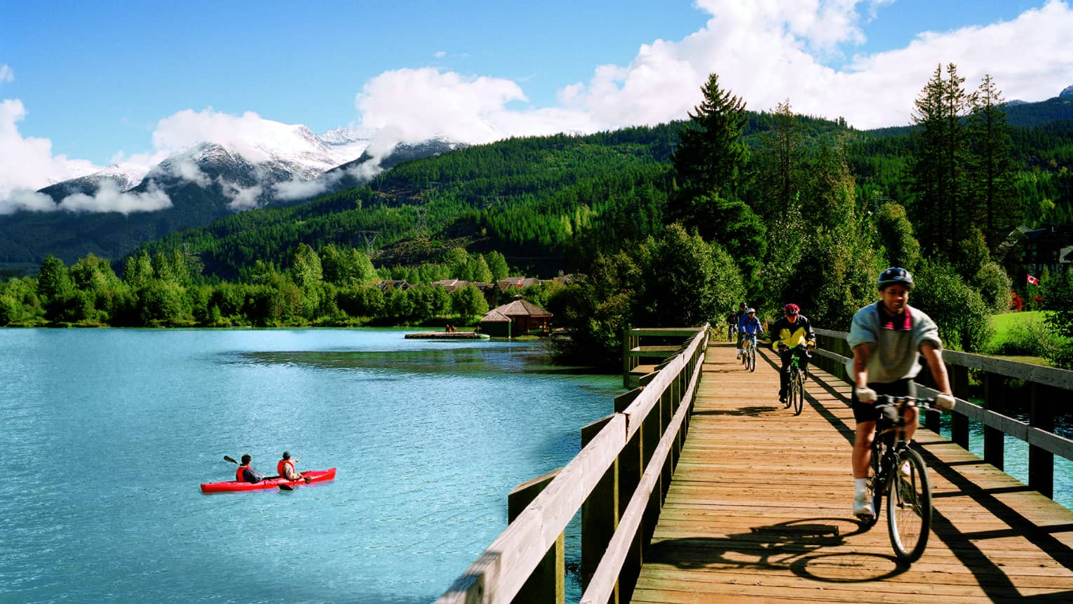 Two people in red kayak in river below green mountain, cyclists ride bikes across wood bridge
