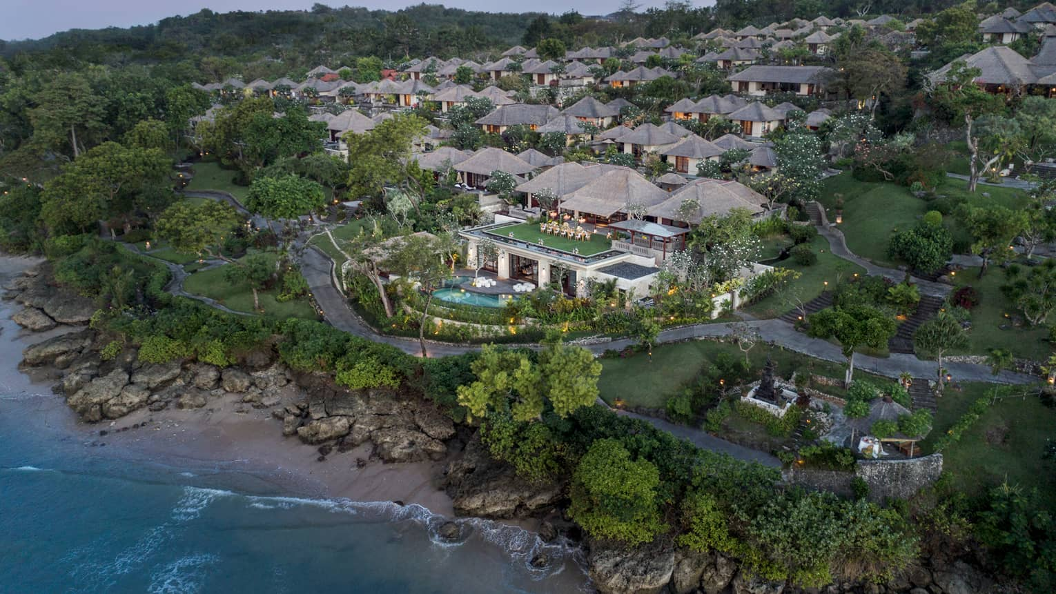 Aerial view of Bali at Jimbaran Bay resort and villas at sunset, overlooking rocks, sand beach and ocean