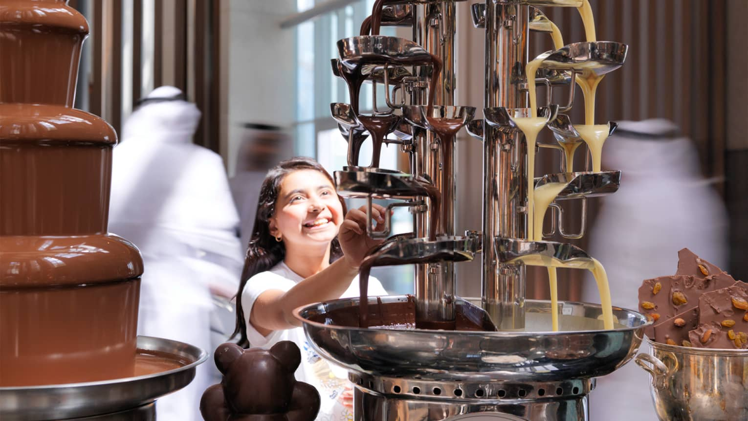 Smiling young girl reaches up tabletop fountain as melted chocolate cascades down