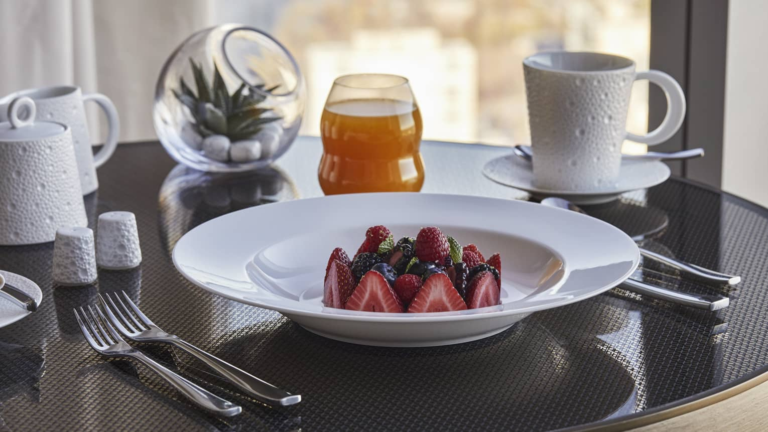 A close up in-room dining detail of strawberries and blueberries in a white porcelain bowl along with a cup of coffee and juice