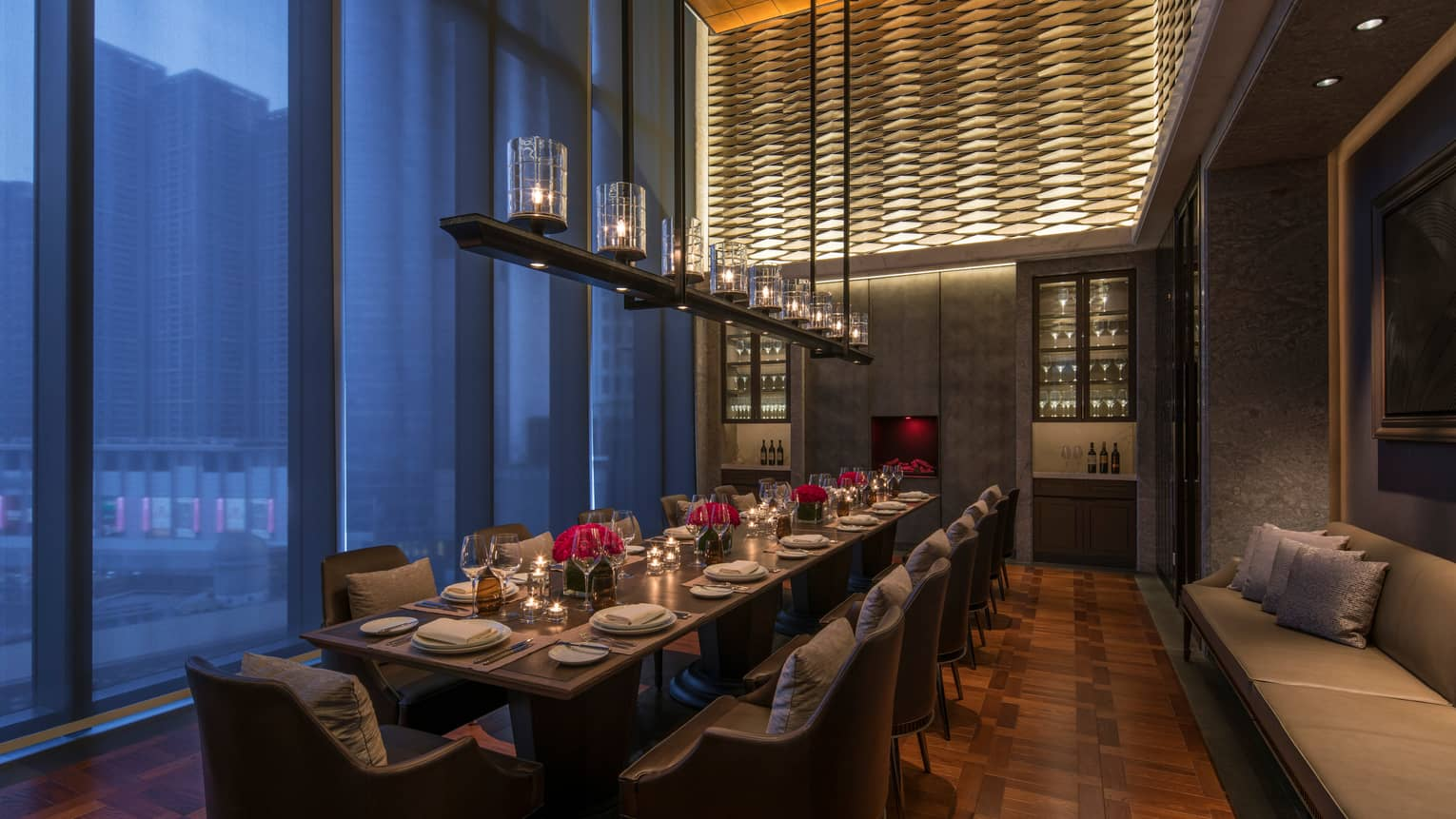 Long private dining table under row of glowing lanterns, tall windows at dusk