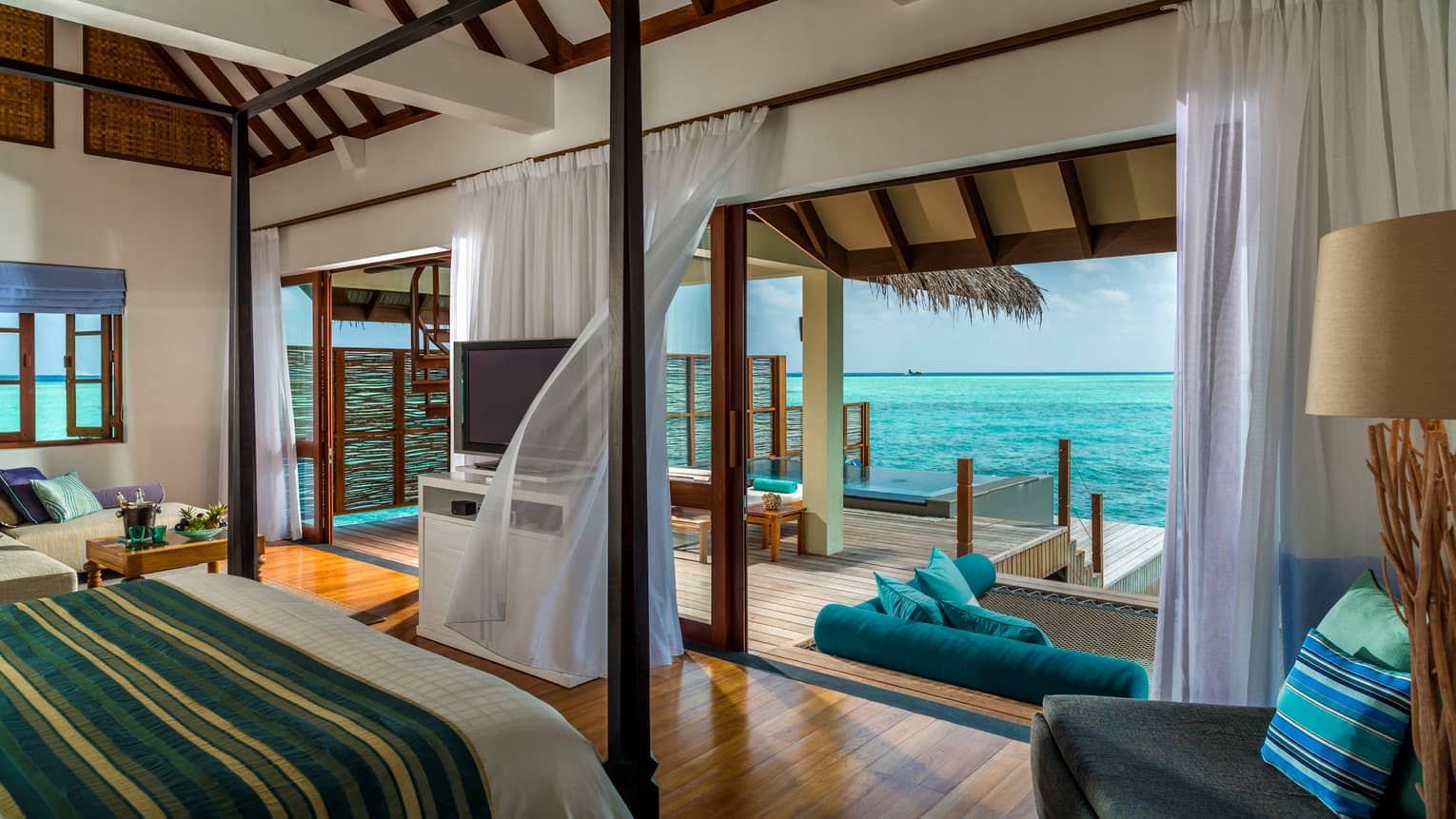 Sunrise Water Villa with Pool poster bed across from open wall to patio, sheer curtains in breeze