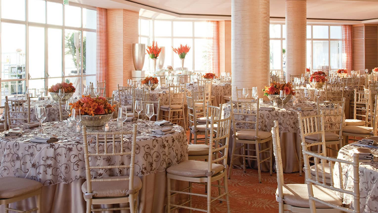 Sunny LaPacifica Ballroom dining tables under pink pillars, sunny floor-to-ceiling windows