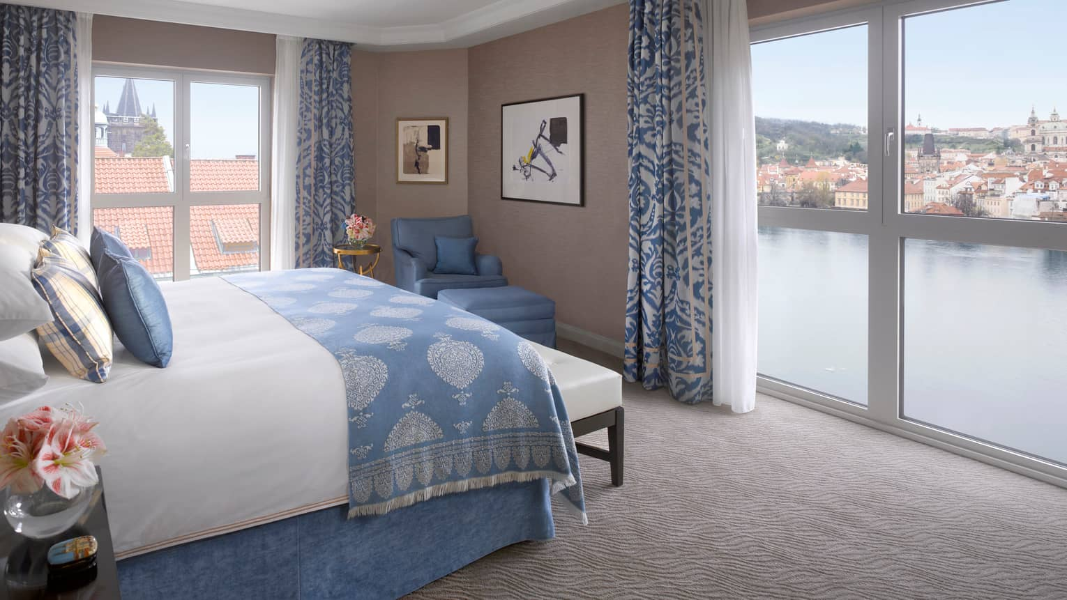 Premier Suite bed with blue blanket, pillow accents, in front of floor-to-ceiling corner windows overlooking Vltava River