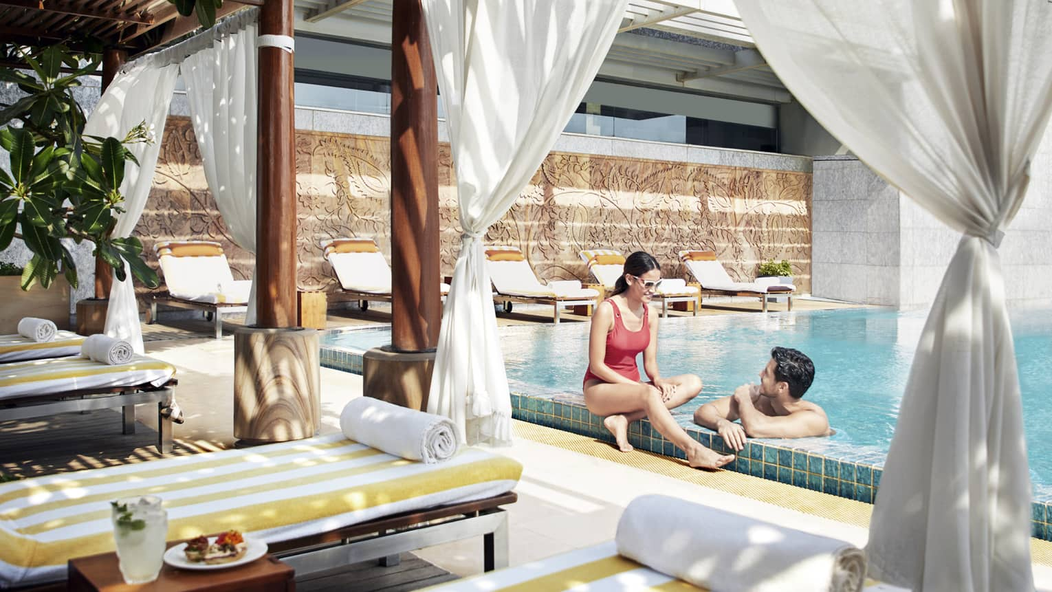 A couple lounges in the pool near a shaded cabana with fresh fruit
