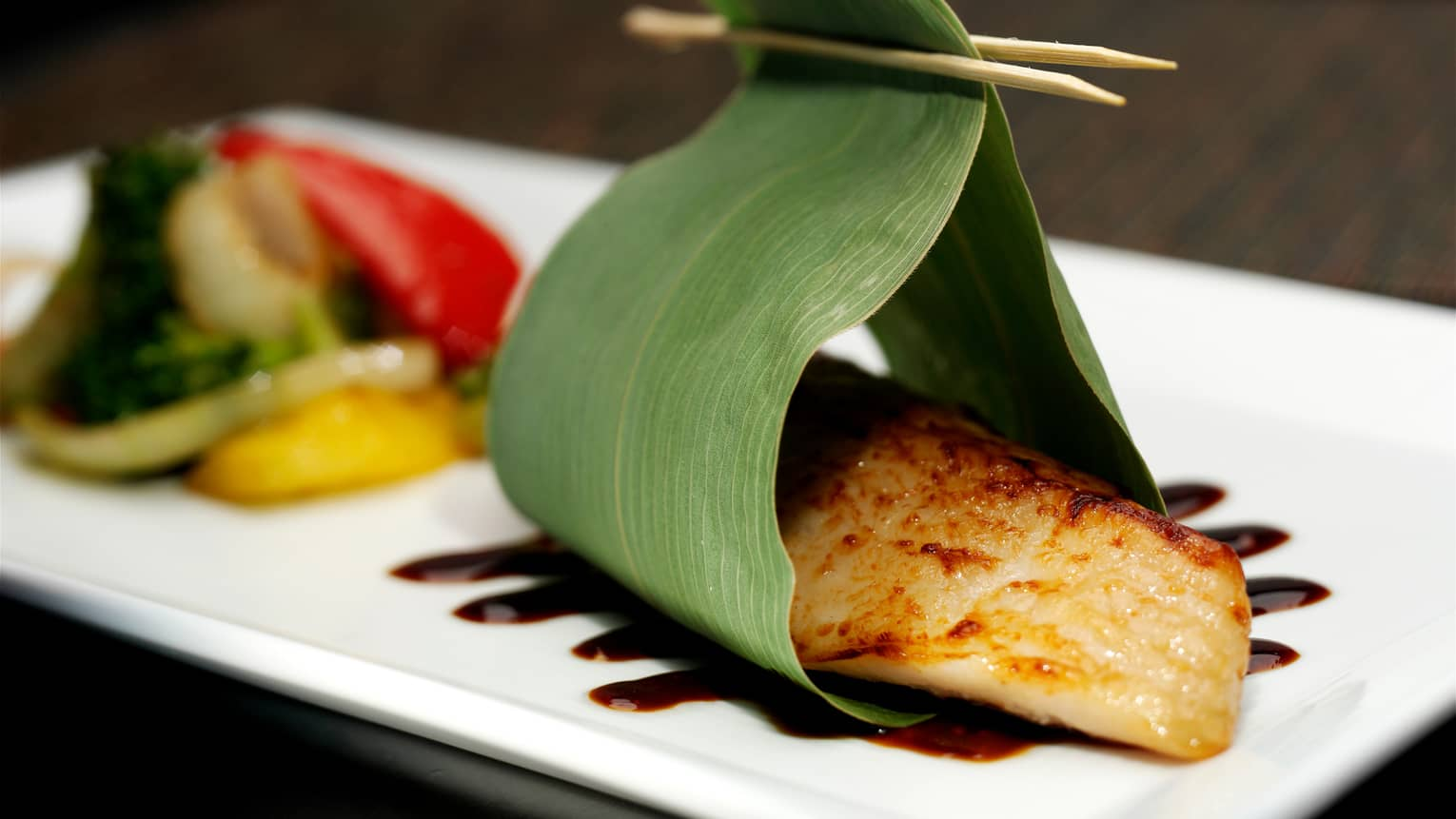 Miso Black Cod filet wrapped in green leaf on white platter with sauce, vegetables