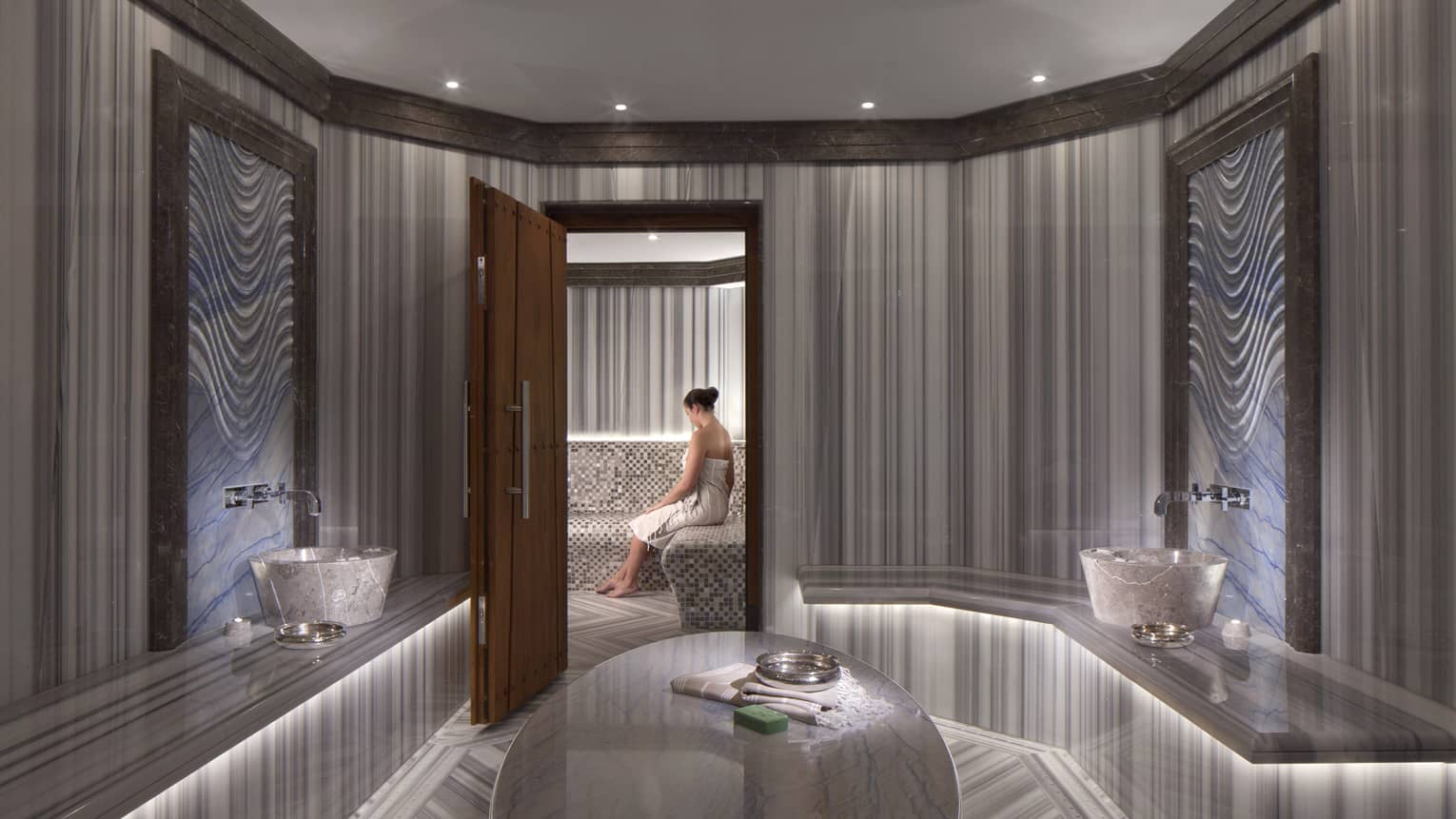 Elegant marble spa room with open wood door where woman wearing towel sits on bench