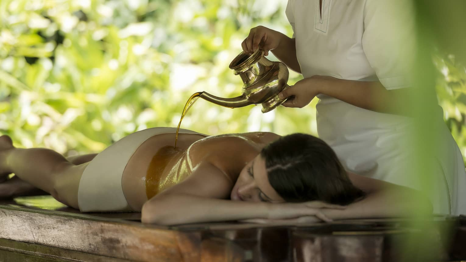 Spa staff pours hot oil from teapot over woman's bare shoulders as she lies on table