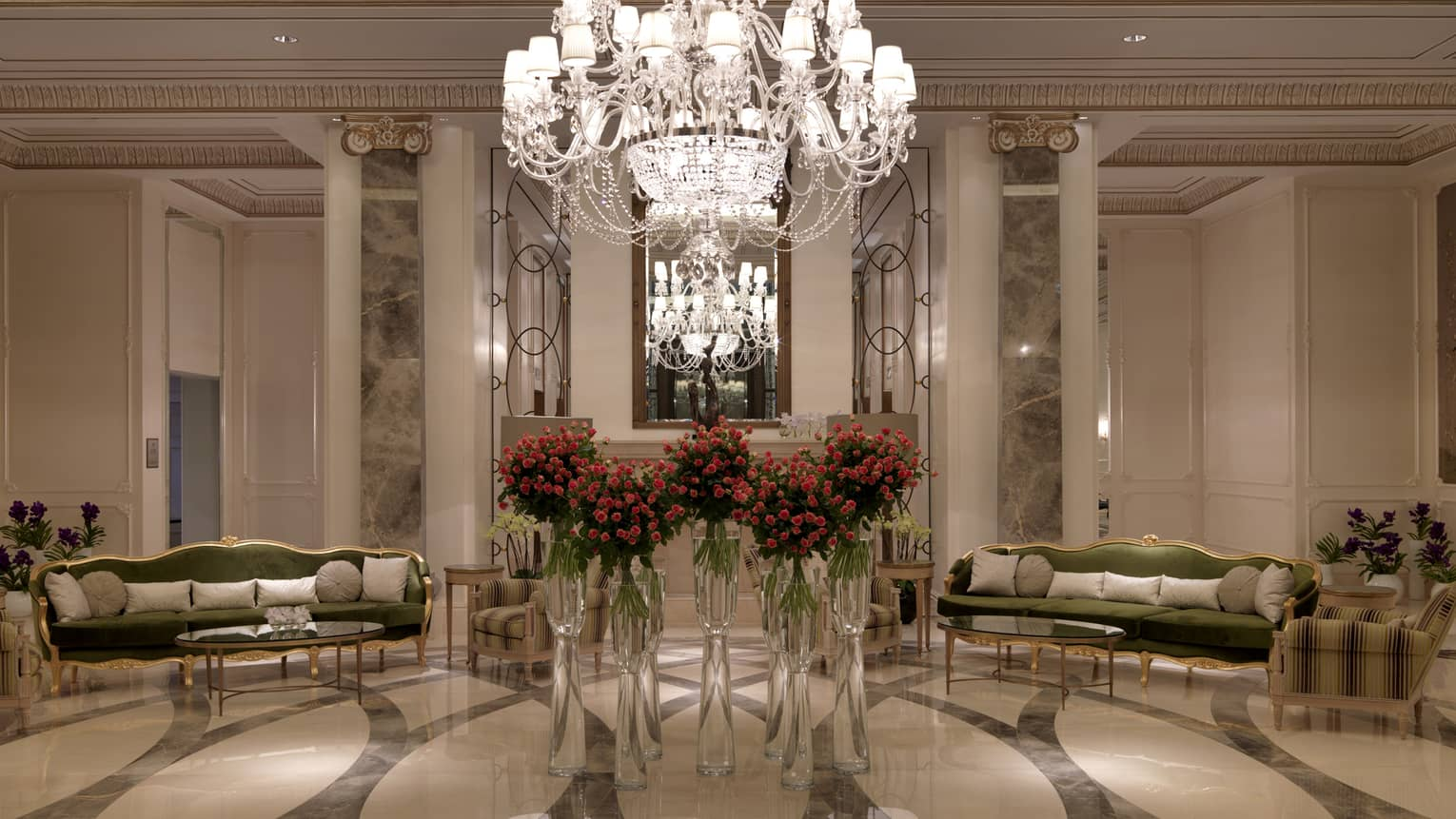 Foyer with large crystal chandelier over flowers in vases, velvet sofas