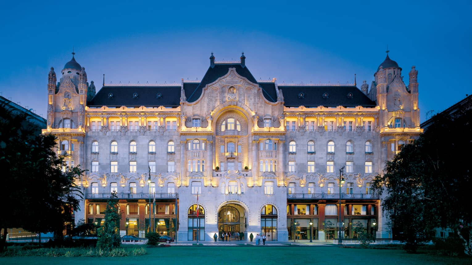 Art Nouveau style exterior of Four Seasons Hotel Gresham Palace Budapest at dusk, lights