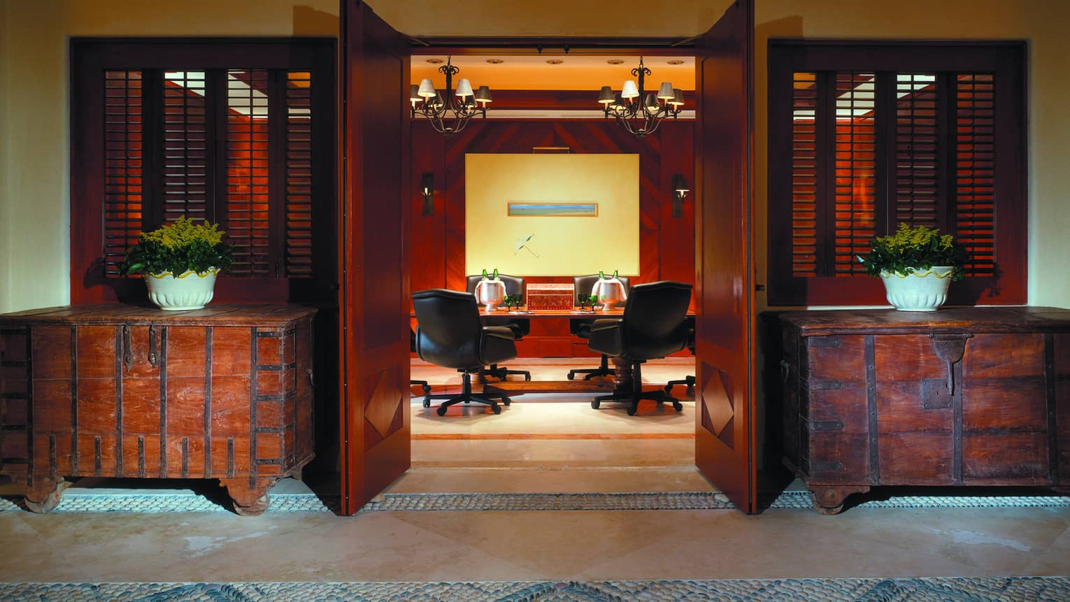 Rustic trunk cabinets flank open doors to Tau meeting room, table