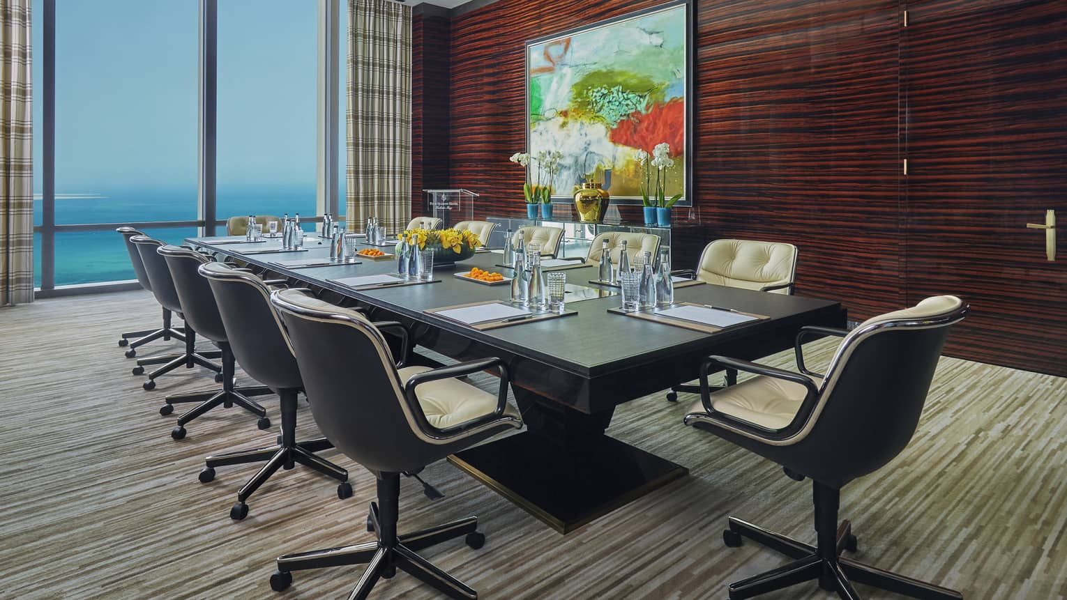 Boardroom meeting table lined with swivel chairs by wood wall with large painting, window