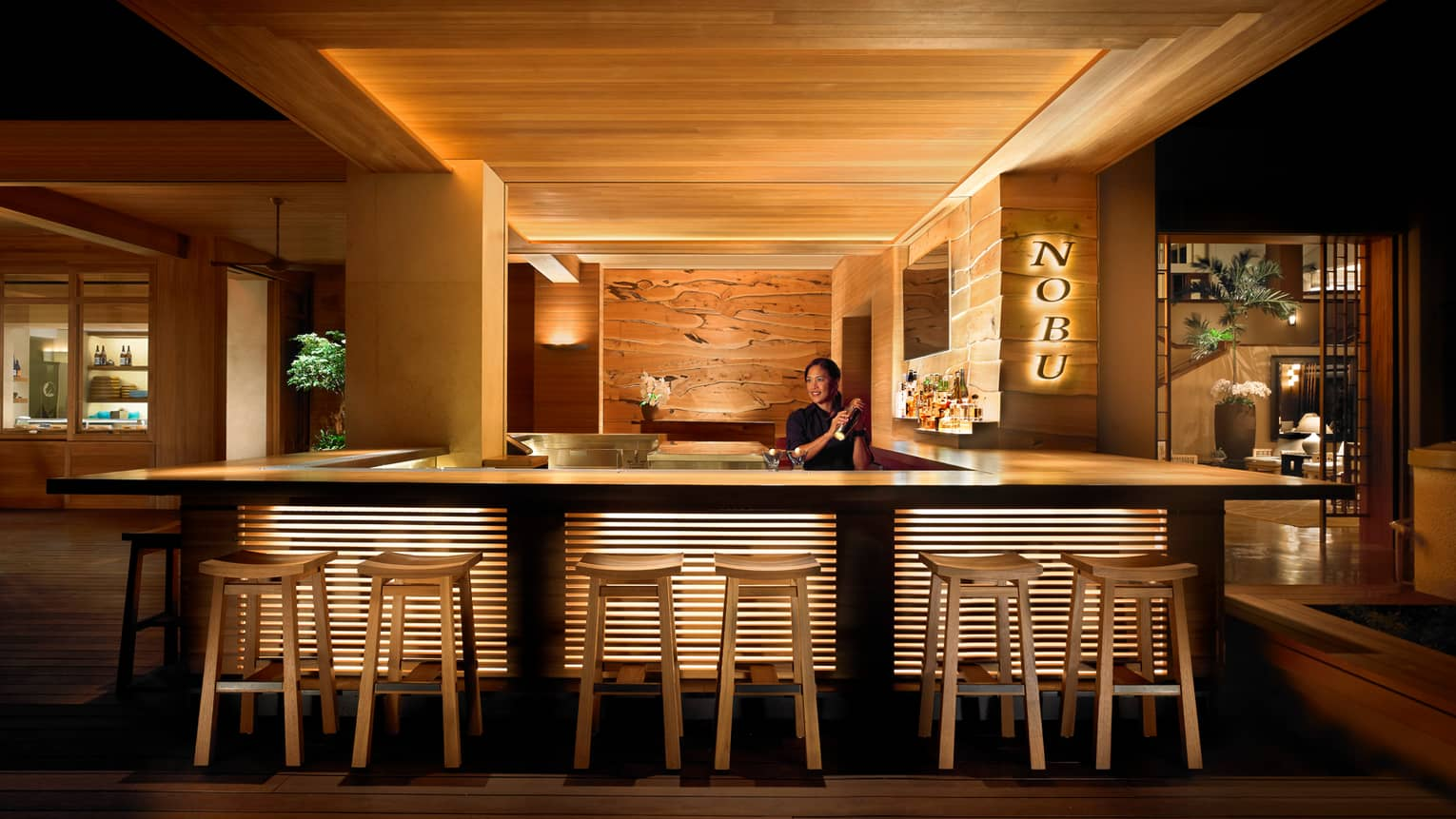 Bartender shaking cocktail behind stool-lined bar at NOBU restaurant