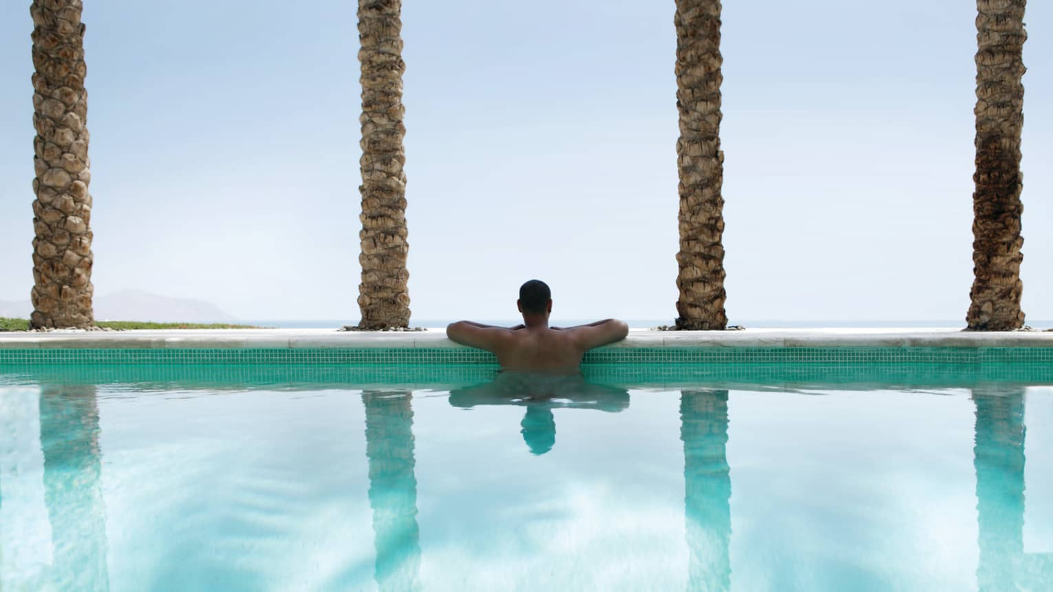 Back view of man resting arms on outdoor swimming pool ledge lined with palm tree trunks
