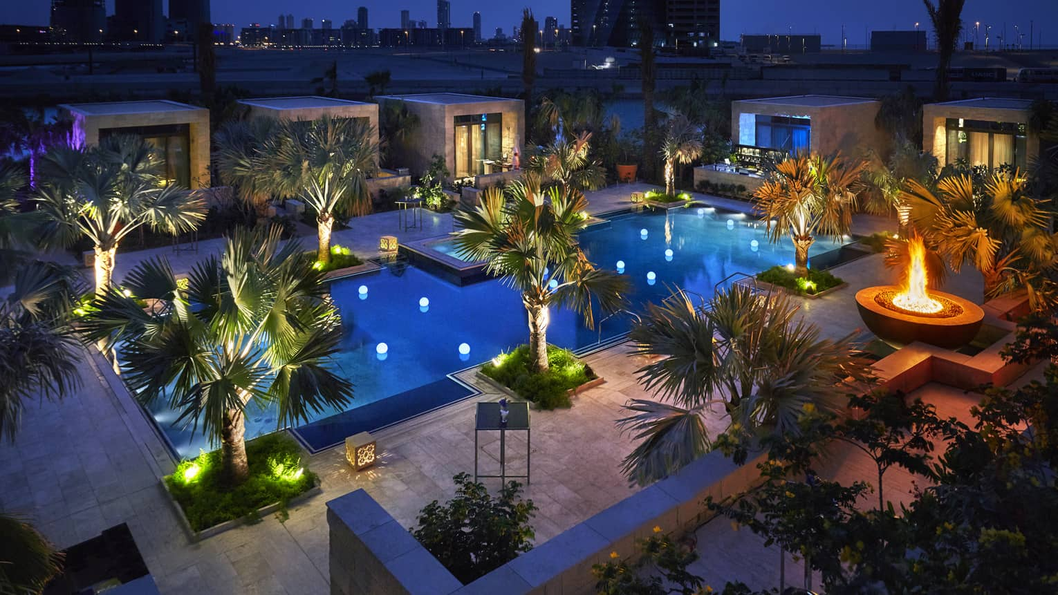 Aerial view of swimming pool, palm trees at night with lights, patio with large outdoor fireplace