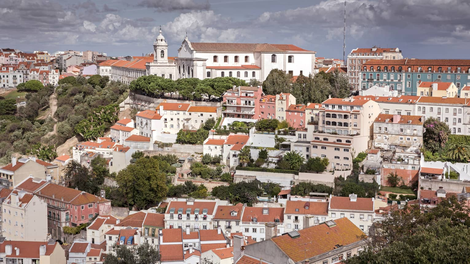 Aerial view of Lisbon city with white cathedral, buildings with red rooftops