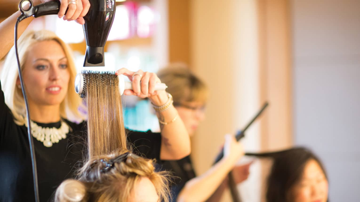 Hairstylist with hairdryer pulls back woman's hair with round brush in salon