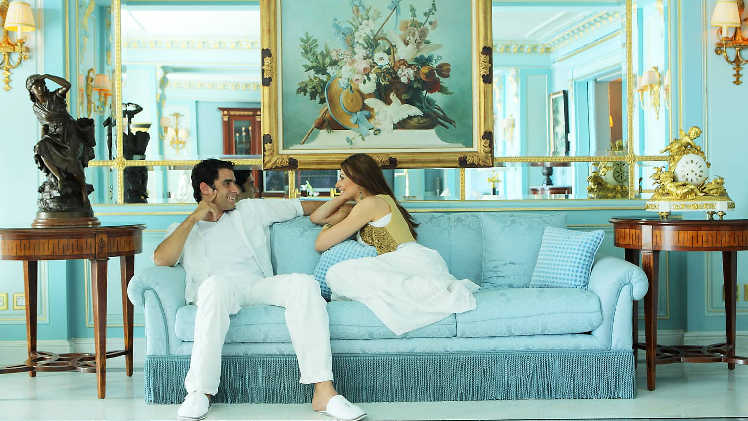 Man and woman smile, relax on blue sofa in Presidential Suite below large mirror, painting, beside statues
