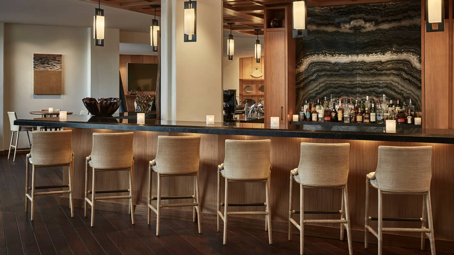 Wicker stools line Hokulea bar with lights, liquor bottles on shelves by wave-like pattern wall