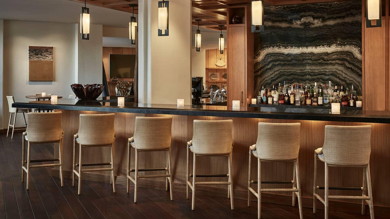 Wicker Stools Line Hokulea Bar With Lights Liquor Bottles On Shelves By Wave Like