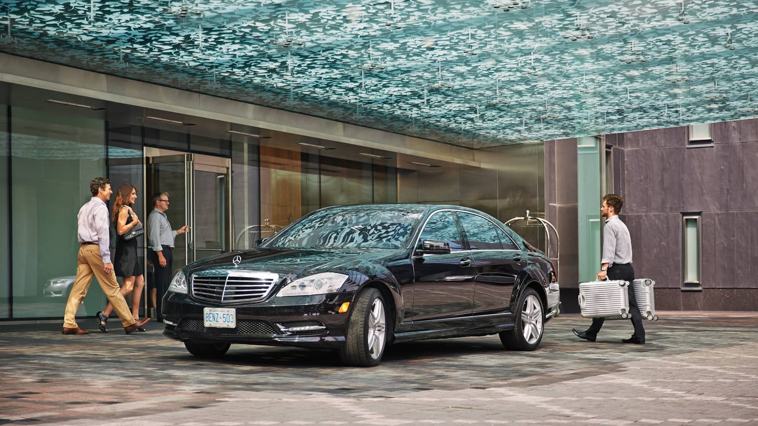 Guests exit through hotel lobby doors to black luxury car, man carries suitcases