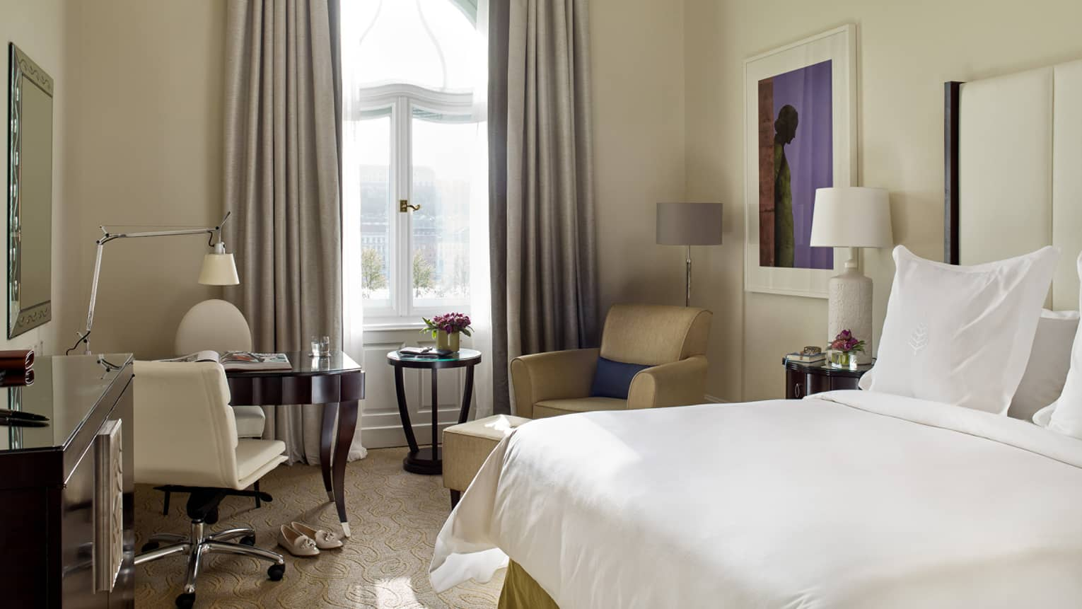 Danube River-View Room bed with white linens, cream-coloured desk chair and armchair, tall picture window, curtains