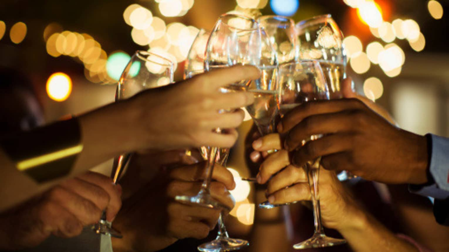 A group of guests clink their glasses of champagne together on a patio with twinkle lights