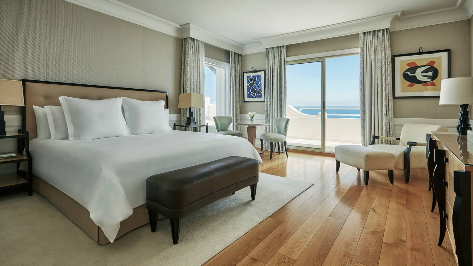 Palace Sea-View room with white bed, leather bench, dining table, armchair by balcony