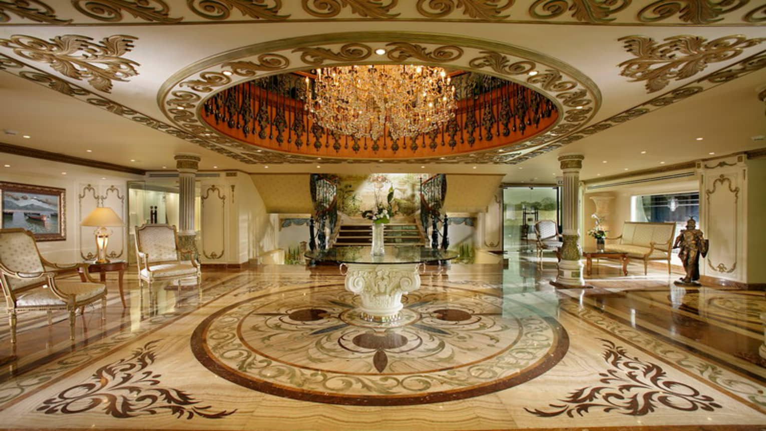 Large crystal chandelier in recessed dome ceiling over marble hotel lobby floor