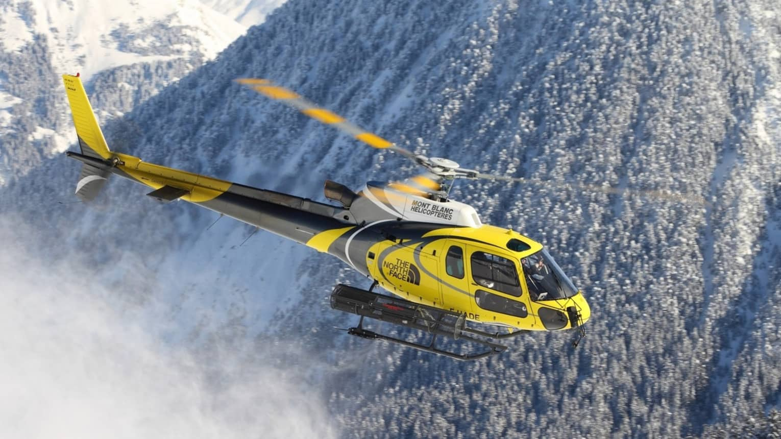 A yellow helicopter flies through a snow covered mountain in the swiss alps
